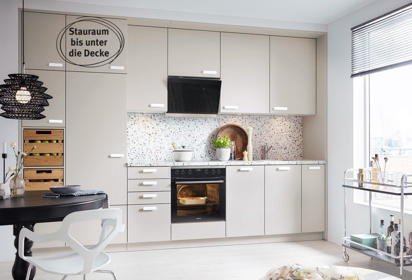 Einbauküche mit sandgrauen Fronten, Arbeitsplatte in Terrazzo Nachbildung und Keramik-Griffen.