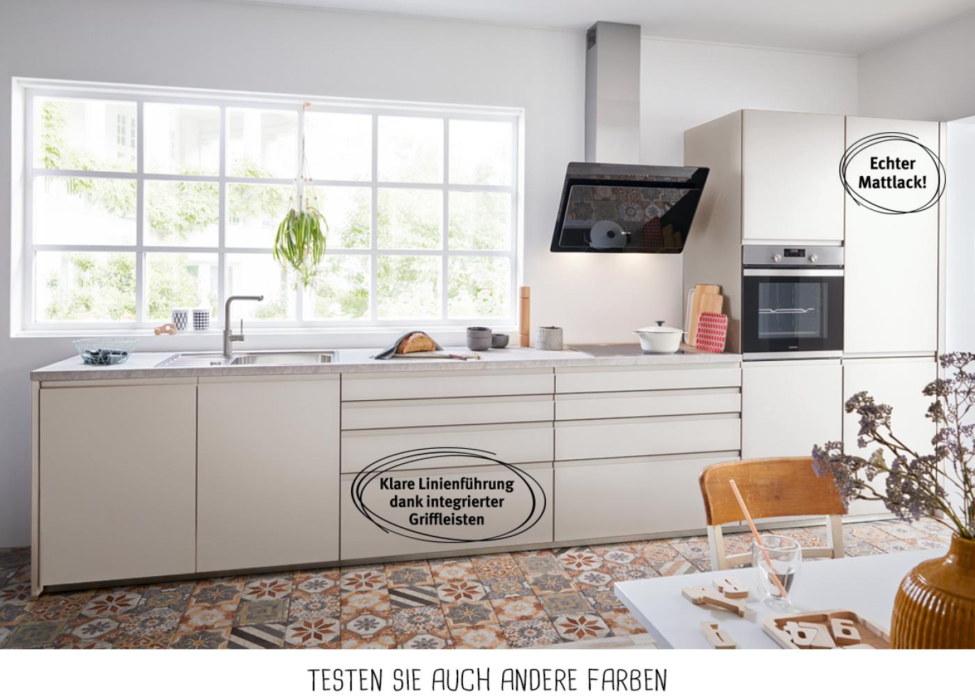 Design-Küchenzeile mit Fronten in Sandgrau und reduzierten Eingriffleisten.