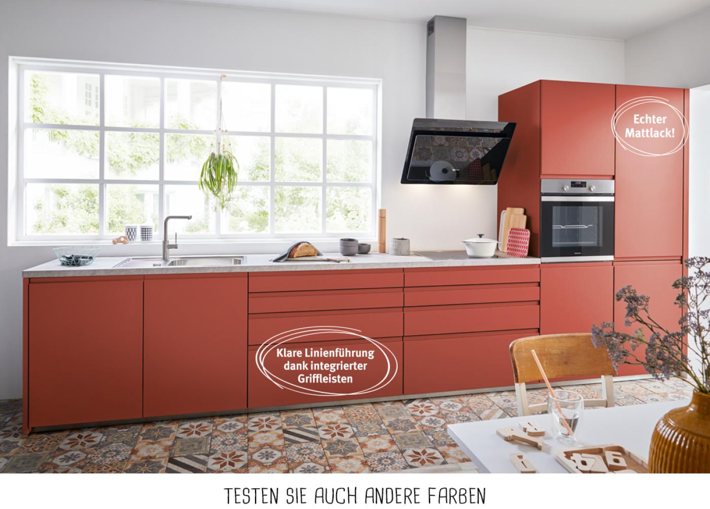 Design-Küchenzeile mit Fronten in Terracottarot und reduzierten Eingriffleisten.